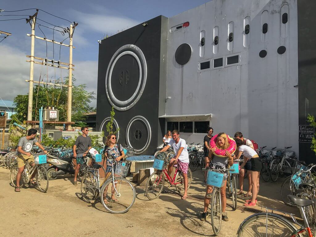 Group of people bikes in front of the Song of Travel Hostel, in Mianmar